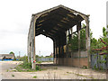 """Dist:0.2km<br/>This abandoned concrete-framed shed has overgrown railway tracks leading towards it from the adjacent Plumstead sidings [[1848634]].  It is wide enough to have housed two """"roads"""" (tracks). But there are also references online to the Royal Arsenal's internal railway system having left the main line about this point, so I am unsure whether this a building would have belonged to British Rail or the military."""