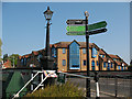 TQ1777 : Signpost and lamppost by Brentford Bridge by Stephen Craven