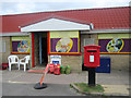 NU2329 : Post box outside convenience store, Beadnell by Graham Robson