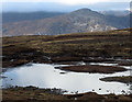 NN5368 : Peaty pool south-west of Stob an Aonaich Mh&ograve;ir by Trevor Littlewood