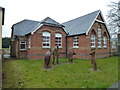 TF3427 : Statues outside the old school in Saracen's Head by Richard Humphrey