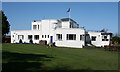 Dist:0.4km<br/>With an Art Deco feel to it, the club house was designed by John Logan and dates from 1937. The right-hand wing seems to have been altered by the addition of a modern roof and windows.