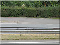 Dist:0.7km<br/>Looking across the A5119 dual carriageway and layby to a hole in the hedge wherein hides an old milestone [[4121937]] The milestone was covered in ivy when I found it, so anyone looking for it in the future will probably be faced with the same problem. The layby is, in fact, the old A5119 as the road has been widened on the north west side.