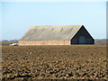 TG4107 : Big shed in crop field by Evelyn Simak