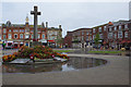 Strand Gardens, in the centre of Exmouth and seen here on a wet day, is dominated by the grade II listed war memorial. The names of the fallen were only added to the base of the cross in 2007.