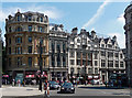 """A busy group on the east side at the Trafalgar Square end of Whitehall, all late Victorian or Edwardian. At the corner is Trafalgar Buildings, by F. and H. Francis, 1882. Next door, nos. 3-5, is by Nelson & Innes, 1864, built as a bank but """"horribly cut up in C20"""". Grade II listed. Then nos. 7-13, by Alfred H. Hart, 1902, built as the Canada Emigration Office. Finally, the triple-gabled no. 15, by Ewan Christian, 1884, for bankers Messrs Cox & Co (the smaller right-hand gable is an extension of 1900)."""