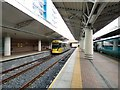 SJ8185 : Tram and train at Manchester Airport by Gerald England