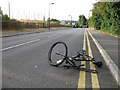 Dist:0.2km<br/>Wreck of a mountain bike left on the road.  It will no doubt make its way to the recycling centre, the gates of which are visible at the end of the road.
