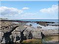 NU2033 : Rocky beach south of  the dunes near Bamburgh Castle by pam fray