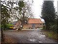 TM2998 : Old Barns at Kirstead Hall farm by Ashley Dace