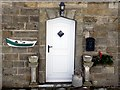 NZ7618 : Doorway with coble fishing boat planter, Boulby by Andrew Curtis