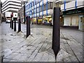 NZ2564 : Bollards, 'Blue Carpet Square' by Andrew Curtis