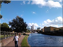 TQ3681 : Sewage ventilation column and Canary Wharf viewed from the Regent's Canal towpath by Robert Lamb