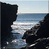 SX3952 : Sharrow rocks with boat at sea by Rob Farrow