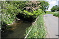 SE2490 : Bedale Beck beside minor road by Roger Templeman