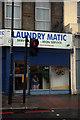 TQ2986 : Woman in laundrette, Holloway Road by Julian Osley