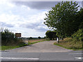 TG2505 : Field entrance & farm track to Arminghall Lane by Adrian Cable