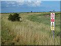TF4952 : Warning sign on the sea bank at RAF Wainfleet by Mat Fascione