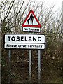 TL2462 : Toseland Village name sign on High Street by Adrian Cable