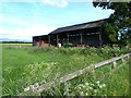 NY5428 : Barn with agricultural machinery beside Moor Lane by Oliver Dixon