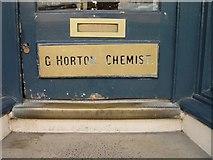 SP0202 : Brass G Horton Chemist sign Market Place Cirencester by Paul Best