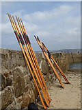 SW3526 : Gig rowers' oars resting on the harbour wall by Rod Allday