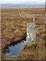 NY8615 : Boundary stone beside fence line by Trevor Littlewood