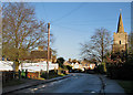 TL4058 : Coton: High Street, school and steeple by John Sutton