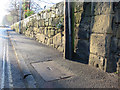 SJ3350 : Stone wall and a bench mark alongside Chester Road by John S Turner