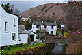 NY2323 : Beck and cottages in Braithwaite by David Martin