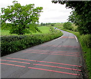 ST9897 : Pink lines across Windmill Road, Kemble by Jaggery