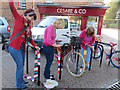SP9211 : Yarn bombing the bicycle rails in Tring Church Square by Chris Reynolds