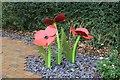 SH7667 : Poppies in Dolgarrog War Memorial Garden by Richard Hoare