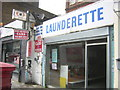 TQ3782 : Launderette and minicab office, near Bow Church by Christopher Hilton