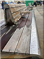 TL1998 : Seat after rain, Cathedral Square, Peterborough by Robin Stott