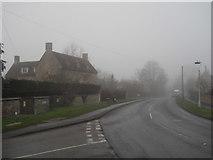 TF1505 : High Street, Glinton, on a foggy day by Paul Bryan