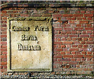 TG2202 : Stone plaque in the wall fronting Common Farm Barns by Evelyn Simak