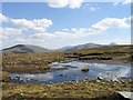 NN2738 : Shallow peaty lochan along ridge of Ben Inverveigh by Trevor Littlewood