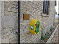 TF0122 : Defibrillator box at village hall by Bob Harvey