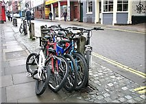 TG2208 : Bicycles by St Swithin's church by Evelyn Simak