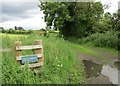 NS7748 : Signpost and overgrown stile at Hailstonemyre by Alan O'Dowd