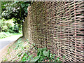 TG3033 : Wickerwork fence and road past Old Hall Farm by Evelyn Simak