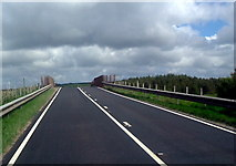 ND1559 : A9 crossing the railway at Georgemas junction by Les Harvey